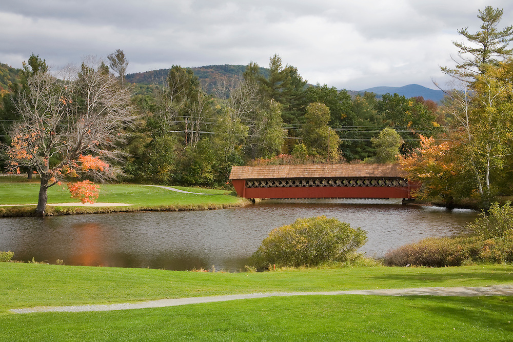 Red covered bridge over pond on golf course.