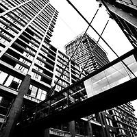 Criss crossing overhead walk ways amongst crowded skyscrapers in a downtown city neighbourhood.