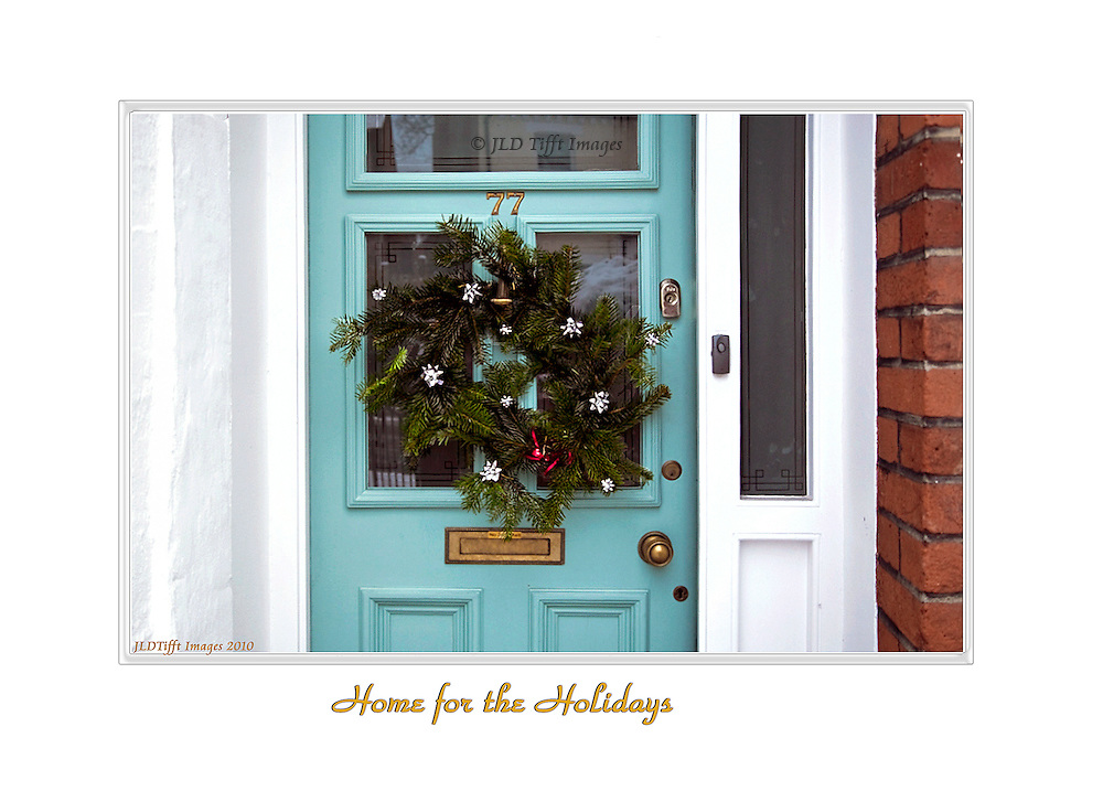 Home-made green wreath scattered with silver ribbon stars hanging on the turquoise door of a house of the Edwardian era, in London.