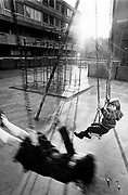 Two kids playing on swings on a housing estate London 1969