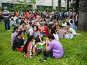 05 AUGUST 2016 - BANGKOK, THAILAND:  Supporters of Yingluck Shinawatra sit on the front lawn of the court building after Yingluck arrived at the Supreme Court in Bangkok. Yingluck appeared in court of Thailand Friday to start her legal defense. She was deposed by a military coup in 2014 and is being tried on corruption and mismanagement charges related to a price support plan for Thai rice farmers that was instituted while she was Prime Minister. More than two years after her government was deposed by a military coup, she is still a popular figure and hundreds of her supporters packed the area around the courthouse to greet her when she arrived at the Court.     PHOTO BY JACK KURTZ