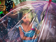 29 SEPTEMBER 2016 - BANGKOK, THAILAND:  A child who lives in Pom Mahakan under an umbrella during a rally in support of the fort's residents. Forty-four families still live in the Pom Mahakan Fort community. The status of the remaining families is not clear. Bangkok officials are still trying to move them out of the fort and community leaders are barricading themselves in the fort. The residents of the historic fort are joined almost every day by community activists from around Bangkok who support their efforts to stay.    PHOTO BY JACK KURTZ