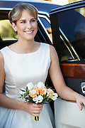Young woman holding bouquet in open door of limousine, portrait