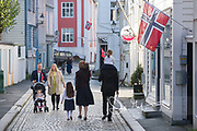 Families walk down a street in Bergen dressed in traditional festive garb in celebration of Syttende Mai, Norway's Constitution Day, celebrated on May 17th.