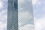 Glass office tower reflects the sky in central Boston, Massachusetts.