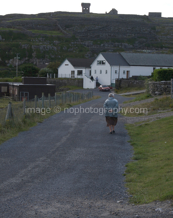 Woman walking down the road on Inis Oirr Island the Aran Islands County Galway Ireland