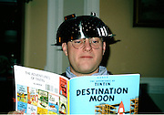 "Young man wears a steel kitchen colander on his head while reading TinTin,. ""Destination Moon.""  Spectacles, earnest expression, and metal ""helmet"" all suggest that he is imagining himself in the story."