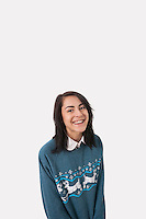 Portrait of happy woman in Christmas jumper against gray background