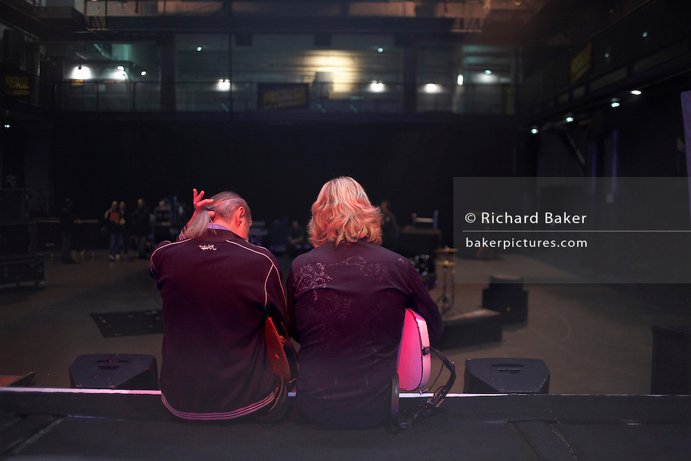 Francis Rossi (left) and Rick Parfitt (right) of Status Quo face an auditorium, with their backs to the viewer  while sitting on the edge of their stage after a sound check in l'Aeronef in Lille, France during their 2007 European Tour. Rossi adjusts his thin pony tail that he has sported since his early days in rock and roll. Parfitt and Rossi are the two original members of the band, having met as school boys in the early 60s. Their distinctive three-chord guitar riff has made them a household name with hits like: Rockin' All Over the World and Sweet Caroline; selling 118 million albums. Over their 40 years of performing, QUO have played over 6000 live shows to an audience of 25 million people and travelling four million miles and spent 23 years away from home..