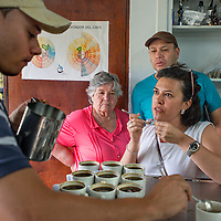 March, 21, 2014 - Quality tasters, Julieta Gonzalez and Oscar Mejia, left, of<br /> Catador Nesperesso Cooperativa discuss the taste profiles of the locally produced coffee processed and stored for world-wide shipment at a co-op, Coopertiva de Caficultores de Andes in the town of Jardin in the Department Antioquia region of Colombia.<br /> Story Summary:<br /> Deep in the verdant valleys of Colombia&rsquo;s Department Antioquia region is Fabio Alonso Reyes Cano&rsquo;s coffee finca. Finca La Siemeona has been in Cano&rsquo;s family for generations. <br /> He and two workers farm the 5-acres of land as his ancestors did, bean by bean.  It is a tradition that has dwindled amid modern day farming techniques that harvest quicker but the selectively picked ripe deep red cherries are picked individually by hand for the best quality. &lsquo;Grain by grain&rsquo; processing allows for greater control over that quality of one of Colombia&rsquo;s top exports.  It also may help save an industry that is seeing firsthand the effects of climate change.<br /> Cano takes pride in the organic process, which he practices out of respect for nature and the land he was born and raised on.  A businessman, Cano keeps his eyes on way to grow but he also takes seriously his role as steward, encouraging biodiversity and employing natural pest control on the finca.  His practices are at odds with other coffee farmers, who have adopted more industrialized techniques. <br /> Climate change threatens a way of life that supports about 92,000 families nationwide and serves as one of Colombia&rsquo;s economic backbones.  Colombian coffee production has declined in recent years due to regional climate change associated with global warming as both the average temperatures have risen and an increase in rainfall.  The trend disrupts the specific climate requirements to grow the Coffea Arabica bean, and a way of life.  (Credit Image: &copy; Eric Reed/ZUMAPRESS.com)