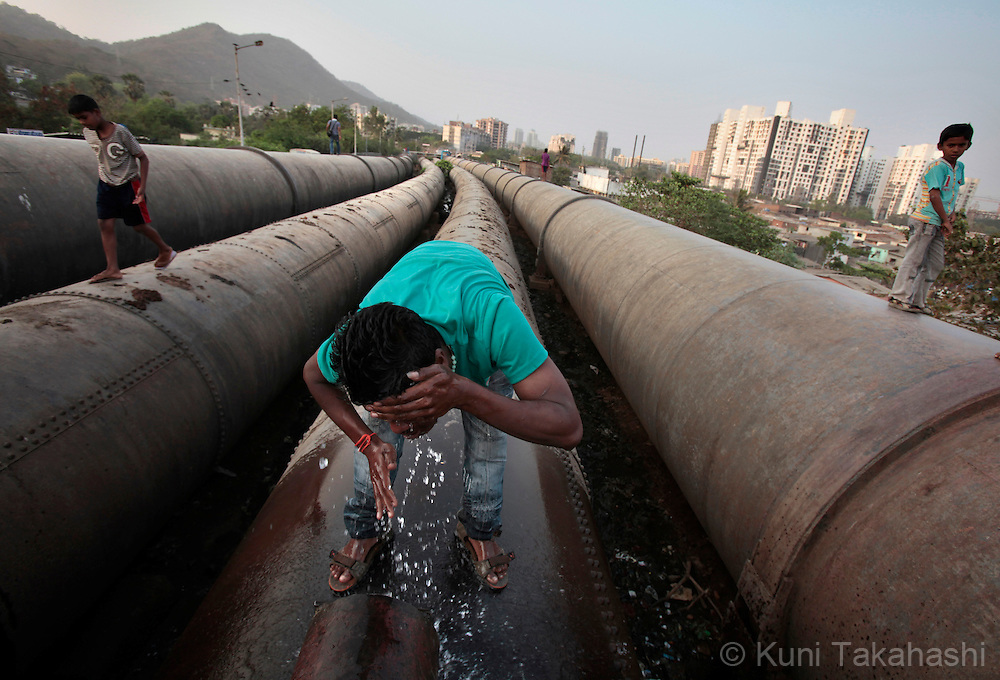 A man use water leaked from the city's water pipeline in Bhandup, Mumbai, India on March 27, 2010. Due to the lack of rain during last year's monsoon, Mumbai is facing one of the worst water shortage in its history and the Municipal Corporation of Greater Mumbai (BMC) has cut 15 % of its water supply in March. Poor maintenance of the pipeline and water thieves, who connect illegal pipes to the city's water line and steal water for sale, are blamed for a part of the shortage.Photo by Kuni Takahashi