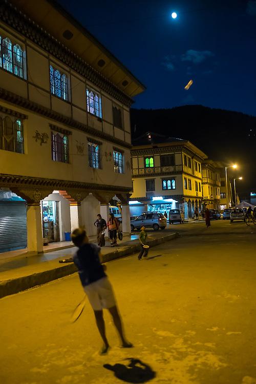 PARO, BHUTAN - CIRCA OCTOBER 2014: Kids playing badminton in the streets of Paro at night.