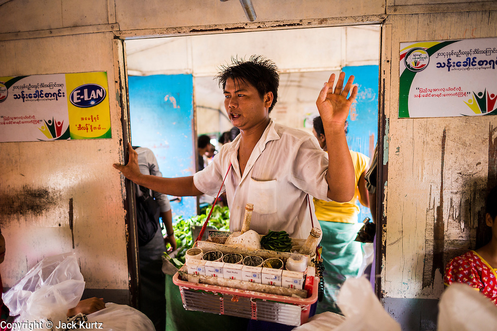 05 JUNE 2014 - YANGON, YANGON REGION, MYANMAR: A betel vendor works the Yangon Circular Train. The Yangon Circular Train is a commuter train that circles Yangon, Myanmar (Rangoon, Burma). The train is 45 kilometers long, makes 38 stops and takes about three hours to make a loop of the city.     PHOTO BY JACK KURTZ