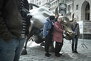 TAURUS TOURIST: Tourists pose with the bull sculpture in Bowling Green near Wall Street. The bull symbolize optimism in the world of economics.