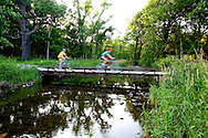 Two bikers speed across a small bridge in the Waterfall Glen Forest Preserve in suburban Chicago.