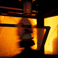 USA, Washington, Seattle, Worker silhouetted by glow of molten steel inside Birmingham Steel Plant