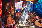 A Naga saadhu resting with his devotees in his tent with sun rays falling on the smoke from the fire in his fireplace at Hindu Festival of Maha Kumbh Mela Haridwar, Uttarakhand, India