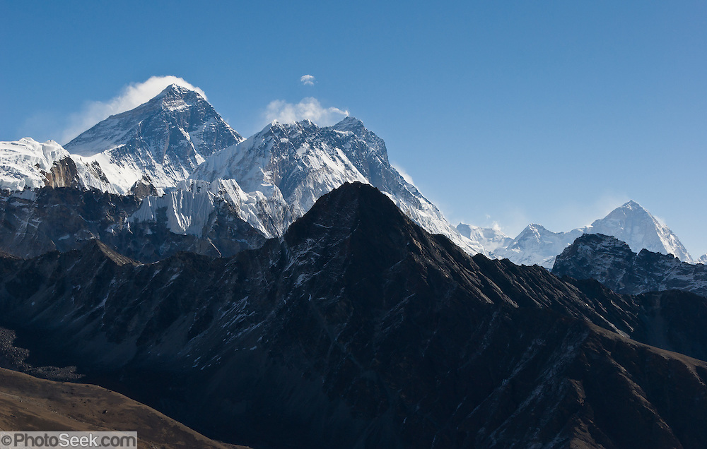"Left to right are: Mount Everest, Nuptse, Lhotse, and Makalu (27,762; world's 5th highest), as seen from Gokyo Ri. Mount Everest (29,035 feet / 8850 meters elevation above sea level, from 1999 GPS measurement), the highest mountain on Earth, was first called Chomolungma or Qomolangma (""Goddess Mother of the Earth"" in Tibetan). In 1865, Andrew Waugh, the British surveyor-general of India named the mountain for his chief and predecessor, Colonel Sir George Everest. In the 1960s, the Government of Nepal named the mountain Sagarmatha, meaning ""Goddess of the Sky"". The mountain, which is part of the Himalaya range in High Asia, is located on the border between Nepal and Tibet, China. Sagarmatha National Park was created in 1976 and honored as a UNESCO World Heritage Site in 1979."