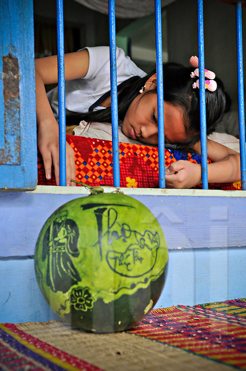 A bored young Vietnamese girl lays on a bed in front of a window, Hue, Vietnam, Southeast Asia