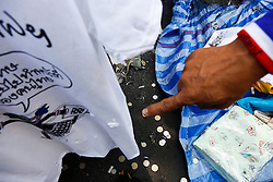 © Licensed to London News Pictures. 19/01/2014. A man points at a T-shirt ripped by shrapnel from a grenade blast .The grenade attack has reportedly injured 28 people at the protest site at the Victory Monument in Bangkok Thailand. Anti-government protesters launch 'Bangkok Shutdown', blocking major intersections in the heart of the capital, as part of their bid to oust the government of Prime Minister Yingluck Shinawatra ahead of elections scheduled to take place on February 2. Photo credit : Asanka Brendon Ratnayake/LNP