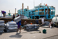 UNITED ARAB EMIRATES, DUBAI - CIRCA JANUARY 2017: Workers loading and old boat in the historic Dubai Creek in Deira.