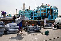 UNITED ARAB EMIRATES, DUBAI - CIRCA JANUARY 2017: Workers loading and old boat in the historic Dubai Creek in Deira.