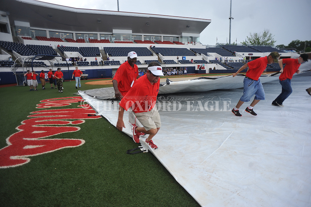 Workers remove a tarp to drain water before the start of the Georgia Tech vs. Washington at the NCAA Oxford Regional at Oxford-University Stadium on Friday, May 30, 2014. (AP Photo/Oxford Eagle, Bruce Newman)