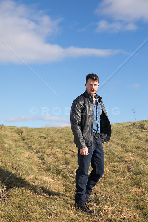 handsome man in a leather jacket on a hillside