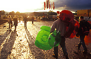 Festival goers making their way accross muddy fields with their inflatable chairs in tow, UK 2000's