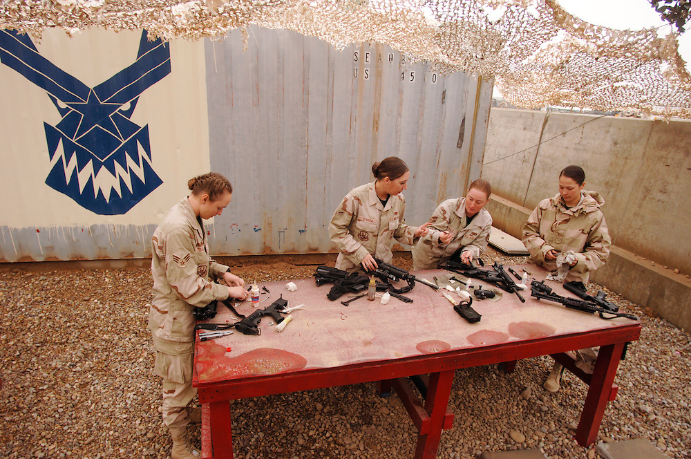 Senior Airman Charity L. Trueblood, Airman 1st Class Nicole P. O'Hara, Staff Sgt. Charnetta J. McDonald, and Senior Airman Candi O. Laury, combat convoy security personnel deployed to the 732 Expeditionary Logistics Readiness Squadron, at Balad Air Base, Iraq, clean their M-4 rifles.  Their duties include driver and gunner on vehicles from HUMVEEs to M-1083 Medium Tactical Vehicles. (U.S. Air Force photo by Master Sgt. Lance Cheung)<br />