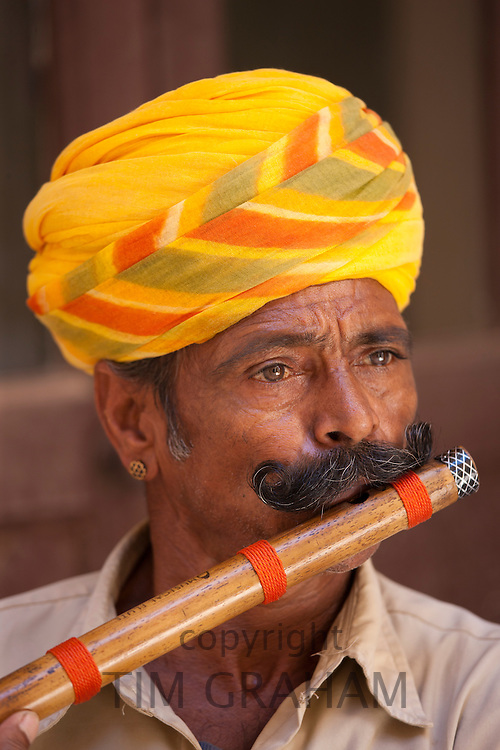 Hindu musician playing flute wind instrument at Mehrangarh Fort at Jodhpur in Rajasthan, Northern India