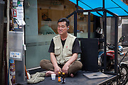 Mann ruht sich vor einer Druckerei auf der Ladefläche eine Motorrads aus.<br /> <br /> Man relaxing infront of a print shop on a load platform of a motorcycle in the center of the korean capital Seoul.