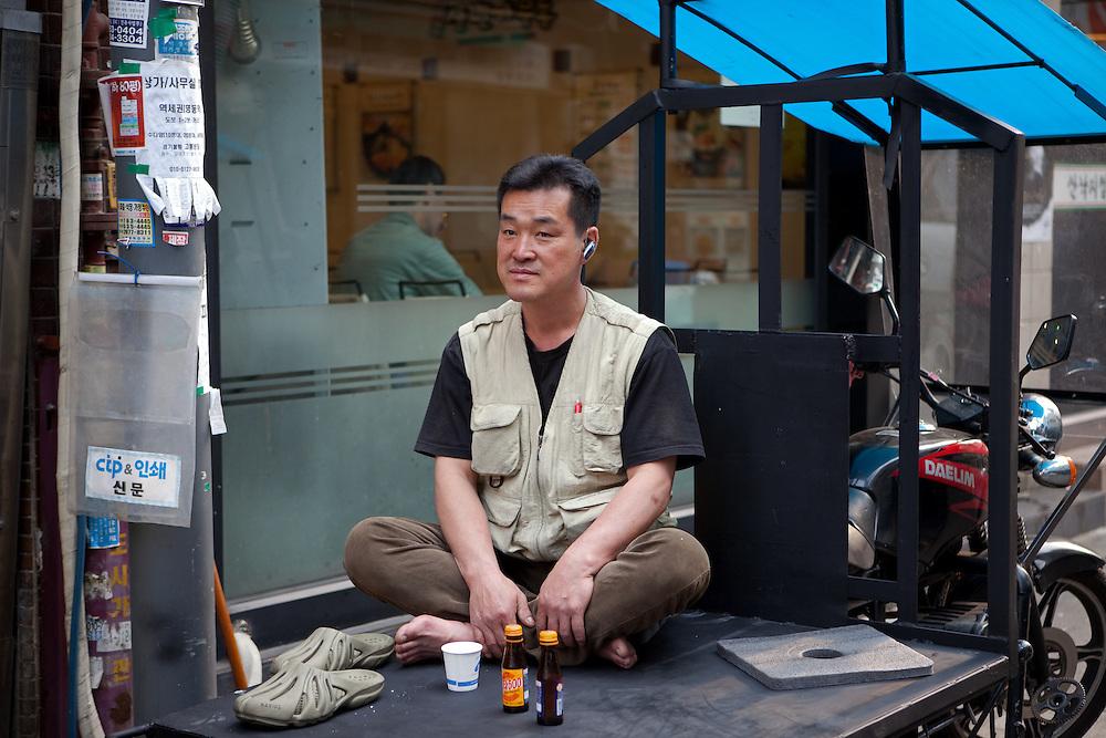 Mann ruht sich vor einer Druckerei auf der Ladefl&auml;che eine Motorrads aus.<br /> <br /> Man relaxing infront of a print shop on a load platform of a motorcycle in the center of the korean capital Seoul.