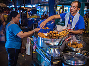 30 JUNE 2016 - BANGKOK, THAILAND:  A grilled meat vendor at his cart in the Pak Khlong Talat sidewalk market. Sidewalk vendors around Pak Khlong Talat, Bangkok's famous flower market, face eviction if they reopen on July 1. As a part of the military government sponsored initiative to clean up Bangkok, city officials have been trying to shut down the sidewalk vendors around the flower market. The vendors were supposed to be gone by the end of March, but city officials relented at the last minute with a compromise allowing vendors to stay until June 30. When vendors dismantled their booths after business on June 30, they weren't sure if they will be allowed to reopen July 1. Some vendors have moved to new locations approved by the government but many have not because they can't afford the higher rents in the new locations.    PHOTO BY JACK KURTZ