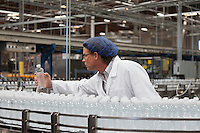 Factory worker examining bottled water