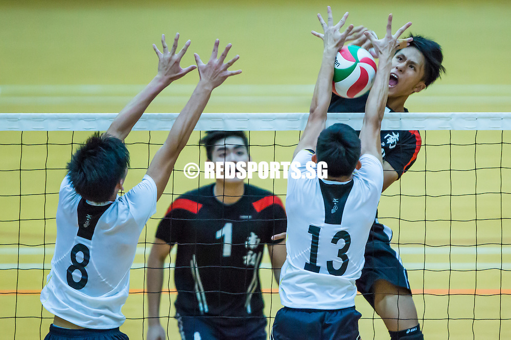 Lim Zi Yang (#4) of Nanyang Junior College spikes the ball against Timothy Tiew (#13) of Victoria Junior College during the final of the National 'A' Division Volleyball Championship at Toa Payoh Sports Hall on May 14, 2014, in Singapore.