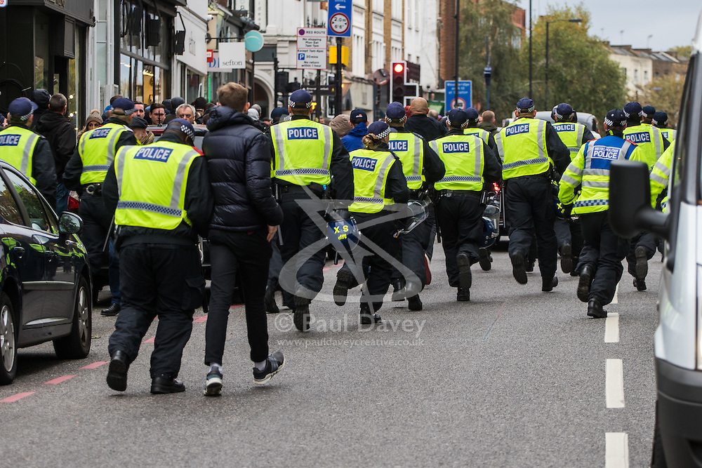 London, November 6th 2016. Police sprint along Islington High Street towards a scuffle after the North London Derby between Arsenal FC and Tottenham Hotspur, that ended in a 1-1 draw.
