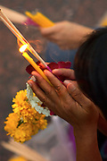 A devout Buddhist holding a candle and flowers pays respects at Erawan Shrine in Bangkok, Thailand.