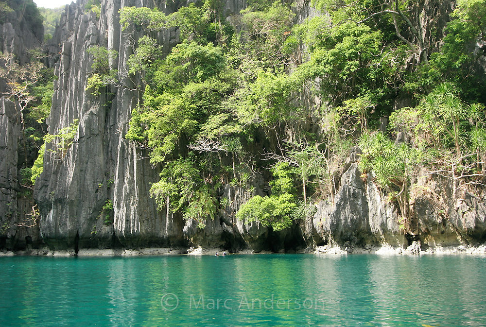 Small Lagoon surrounded by limestone cliffs in the Bacuit Archipelago, El Nido, Palawan, Philippines.