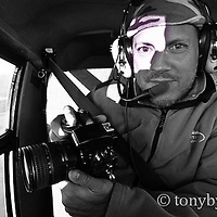 photographer in airplane taking photographs conservation photography - blackfeet oil