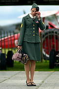 © Licensed to London News Pictures. 16/09/2012. Goodwood, UK .  A woman dressed in military uniform removes an eyelash. People enjoy the atmosphere at the 2012 Goodwood Revival. The event recreates the glorious days of motor racing and participants are encouraged to dress in period dress. Photo credit : Stephen Simpson/LNP