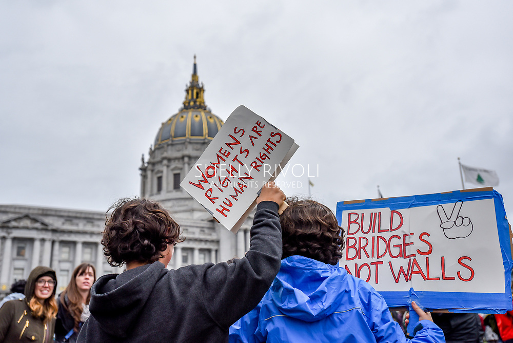 "Two young children stand among the crowd gathering before San Francisco City Hall with signs reading, ""Womens rights are human rights,"" and ""Build bridges not walls."""