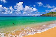 Woman enjoying the blue green waters at Secret Beach (Kauapea Beach), Island of Kauai, Hawaii