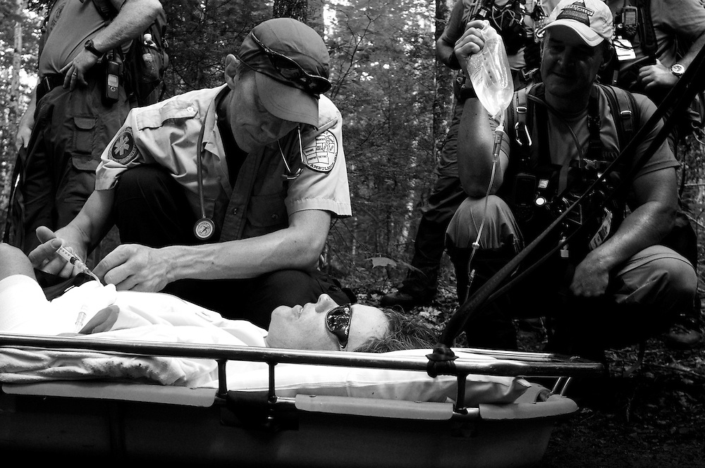 A paramedic from Upper Valley Ambulance, who declined to give his name, injects injured hiker Christina Brownell with medication to keep her comfortable during a break on the slow trek down the Appalachian Trail on Mount Cube Thursday, July 5, 2012. Tom Frawley, right, of Lyme, a volunteer with the Upper Valley Wilderness Response Team, holds a bag of intravenous fluids to keep Brownell hydrated.<br /> Valley News - James M. Patterson<br /> jpatterson@vnews.com<br /> photo@vnews.com