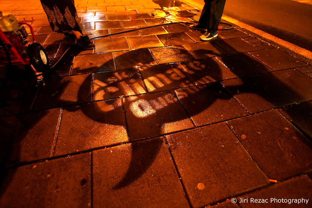 UK ENGLAND LONDON 29APR10 - Activists use a pressure washer and a stencil to do some pavement graffiti on Essex Road in Islington, North London. The reverse clean graffiti method uses water and a pressure washer applied to dirty surfaces to inscribe the Climate Question message onto pavements ahead of the UK general election next weekend...jre/Photo by Jiri Rezac..© Jiri Rezac 2010