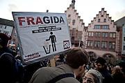 Frankfurt am Main | 30 Mar 2015<br /> <br /> Am Montag (30.03.2015) demonstrierten etwa 40 Menschen unter dem Namen &quot;Freie B&uuml;rger f&uuml;r Deutschland&quot; auf dem R&ouml;merberg in Frankfurt am Main gegen Islamisierung und zahlreiche andere &Uuml;bel, die Gruppe war zuvor unter dem Namen &quot;PEGIDA&quot; aufgetreten. Etwa 600 Menschen protestierten lautstark gegen diese Kundgebung.<br /> Hier: Gegendemonstrant aus dem Umfeld der Partei &quot;Die Partei&quot; mit einem Plakat mit der Aufschrift &quot;FRAGIDA - Frankfurt gegen die Offenbachisierung des Hessenlandes&quot;.<br /> <br /> &copy;peter-juelich.com<br /> <br /> [No Model Release | No Property Release]