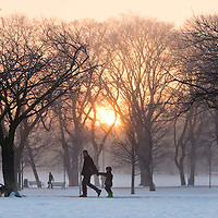EDINBURGH, UK - 8th January 2010:  A man walks with a child  through Edinburgh meadows in early morning sunrise as UK temperatures remain at sub-zero after the Met Office recorded the winter's coldest day yet..Temperatures  plunged to -22.3C in the Highlands.. (Photograph: Michael Hughes/MAVERICK)