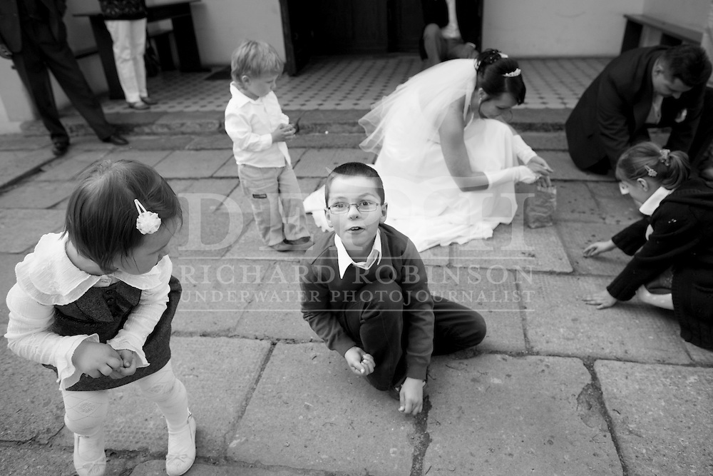 Kids help the bride and groom pick up money thrown at them a Polish tradition that brings wealth to the couple in their marriage..Polish wedding of Izabela Stolarska and Piotr Koziol in the suburb of Marki in Warszawa Poland..Saturday 08 May 2010.Photograph Richard Robinson © 2010.