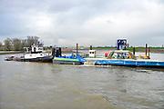 Nederland, Nijmegen, 25-11-2015 De nevengeul aan de overkant van de Waal bij Lent nadert zijn voltooiing. Laatste werkzaamheden. Aan de kant van de drempel, de inlaat, werkt een zandzuiger om de geul op diepte te krijgen. Grootste onderdeel van de vele werken van Rijkswaterstaat om bij hoogwater een betere waterafvoer in de rivier te hebben. Het is een omvangrijk project waarbij onder meer de pijlers van het spoorviaduct een bredere basis kregen omdat die straks in de loop van het water staan. Ook de n325 die vanaf de Waalbrug naar Arnhem loopt is over 400 meter opnieuw aangelegd omdat het talud vervangen wordt door een nieuwe brug met drie gracieuze pijlers. Het dorp veurlent komt op een kunstmatig eiland te liggen met twee bruggen als ontsluiting. Een voetgangersbrug en een andere, de Promenadebrug, voor normaal verkeer. Inmiddels begint de nieuwe kade aan de noordkant van deze geul vorm te krijgen. Ruimte voor de rivier, water, waal. In de nieuwe dijk wordt een drempel gebouwd die stapsgewijs water doorlaat en bij hoogwater overloopt. The Netherlands, Nijmegen Measures taken by Nijmegen to give the river Waal, Rhine, more space to flow during highwater and to prevent the risk of flooding. Room for the river. Reducing the level, waterlevel. Large project to create a new paralel gully, an extra flow of water, so the river can drain more water during highwater. Due to climate change and expected rise, increase of the sealevel, the Dutch continue to protect their land from the water. Foto: Flip Franssen/HH