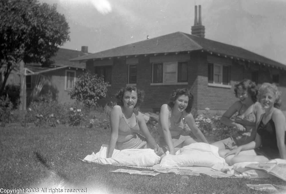 A group of women sunbathe in a suburban housing setting during the late 1940s or early 1950s.